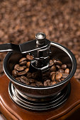 close up of antique coffee grinder with coffee beans