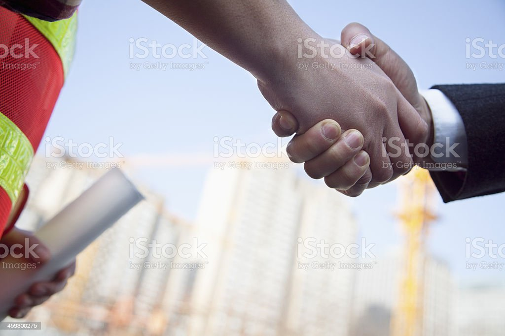 Close up of architect and building contractor shaking hands stock photo