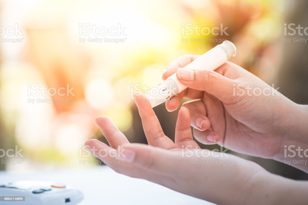 Close up of asian woman hands using lancet on finger to check blood sugar level by glucose meter, Healthcare medical and check up, diabetes, glycemia, and people concept stock photo