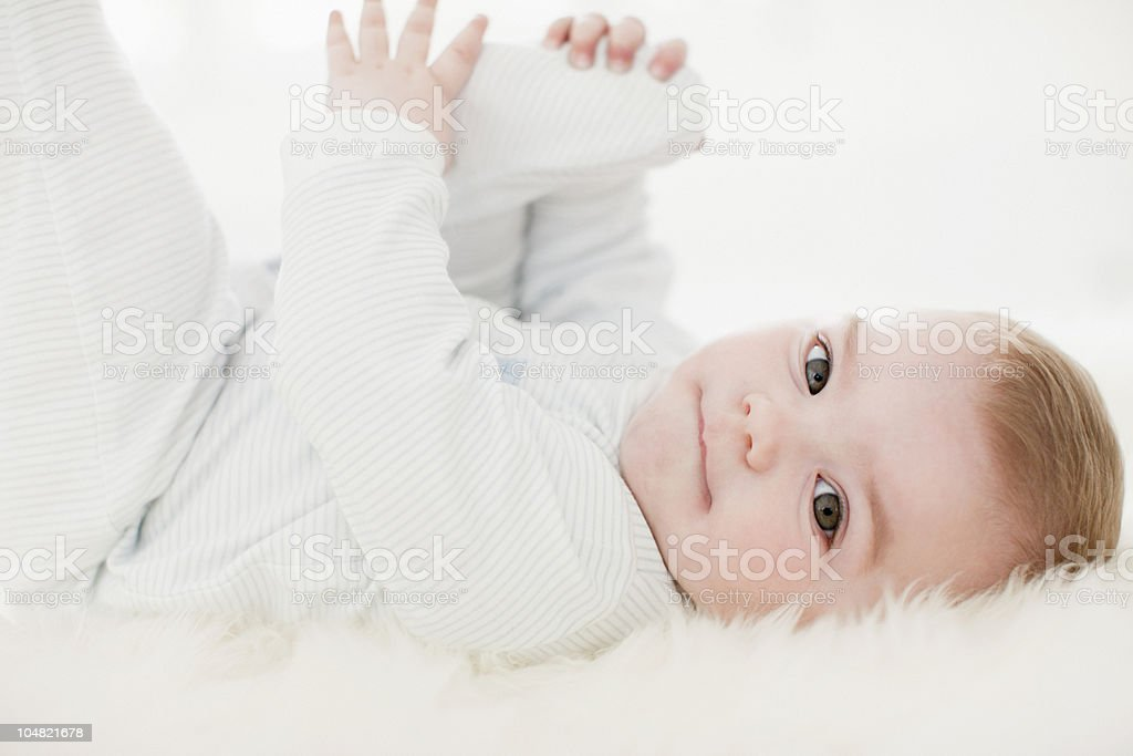 Close up of baby laying on rug stock photo