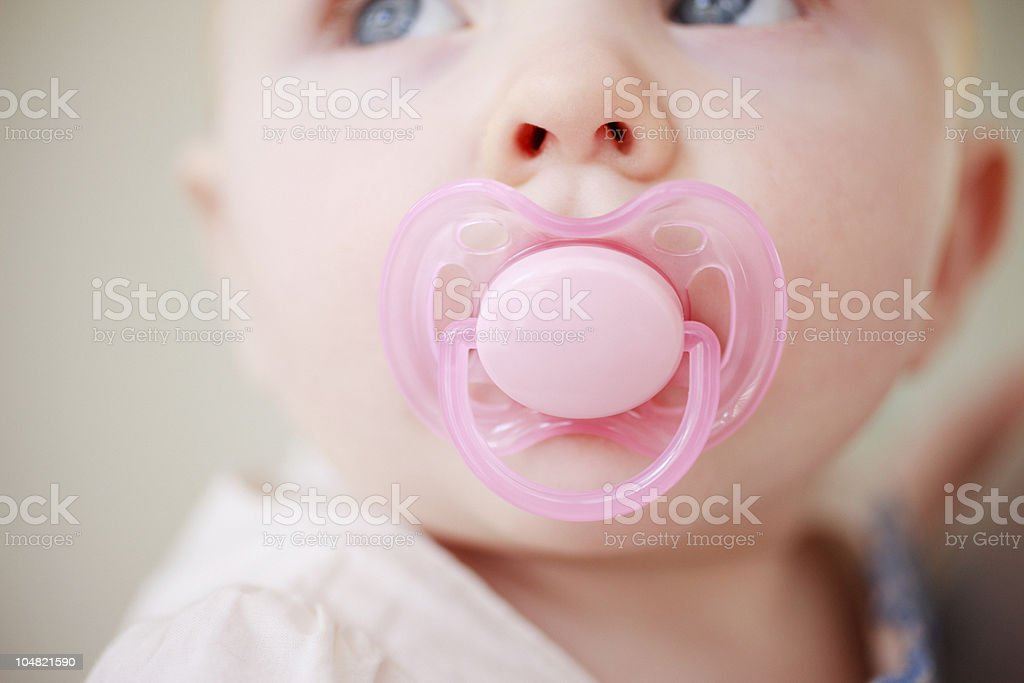 Close up of baby with pink pacifier stock photo