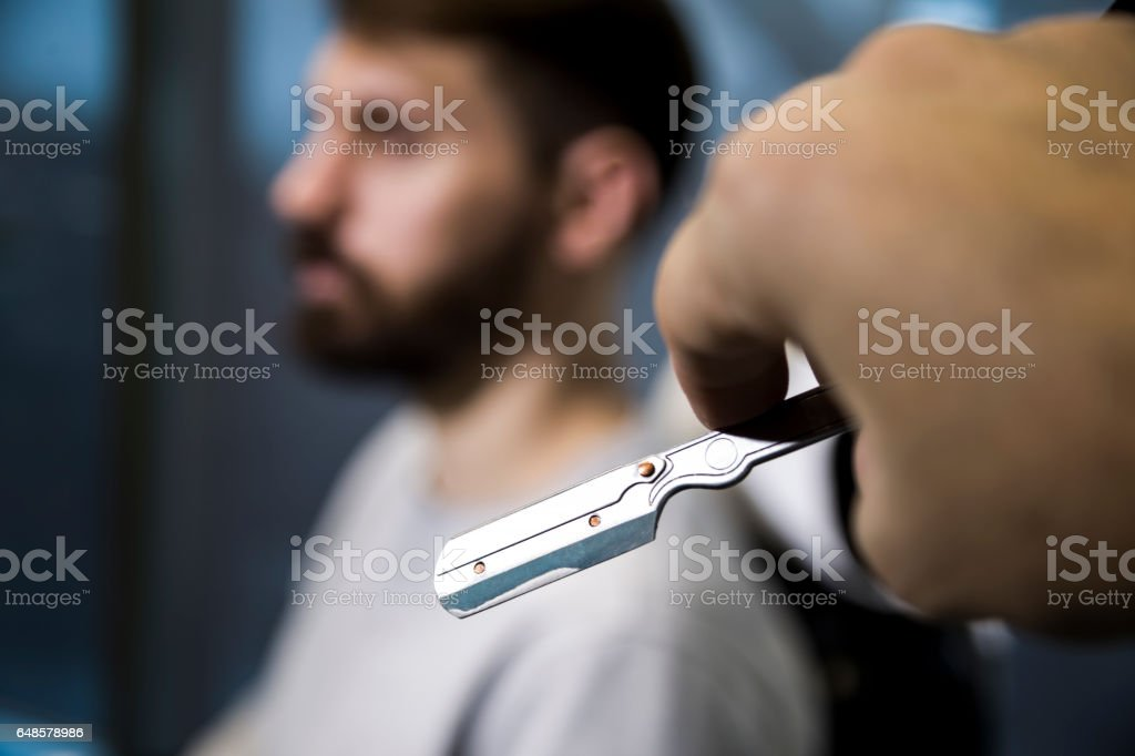 Close up of barber's hand with a blade stock photo