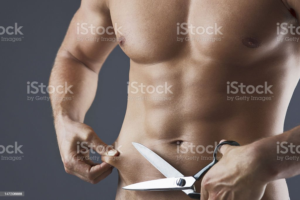Close up of bare chested man holding scissors and squeezing stomach royalty-free stock photo