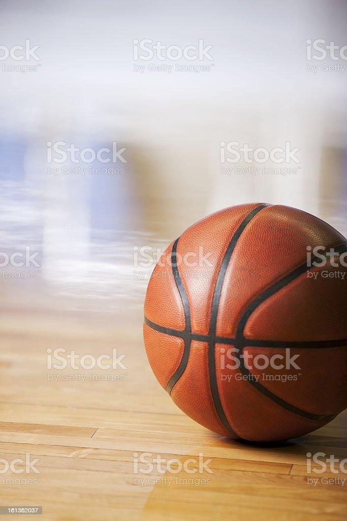 A closeup image of a basketball on a hardwood basketball court with...