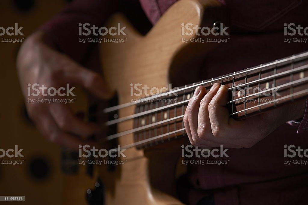 Close Up Of Bass Guitarist Playing Instrument stock photo
