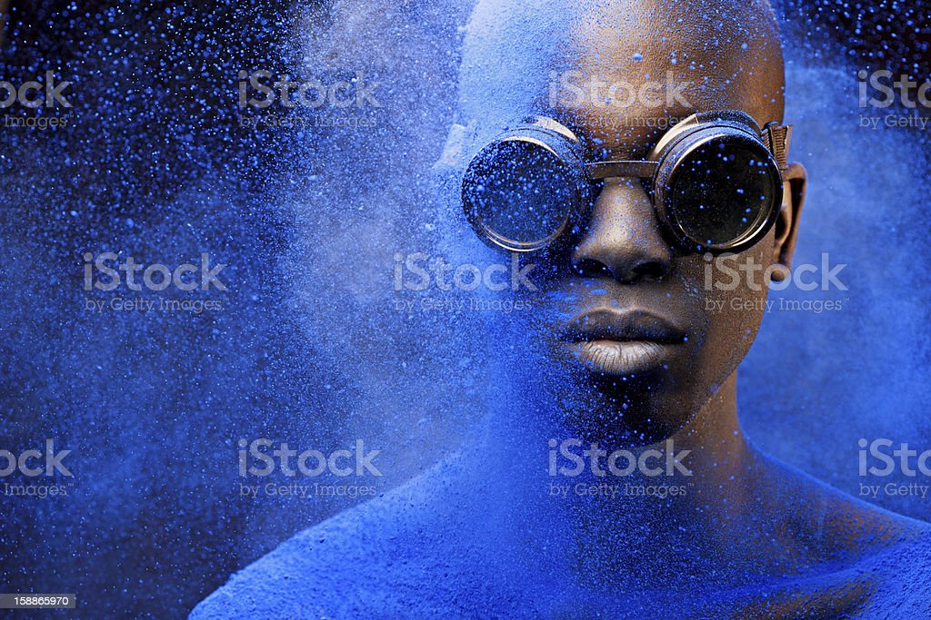 close up of black man covered with blue pigment stock photo