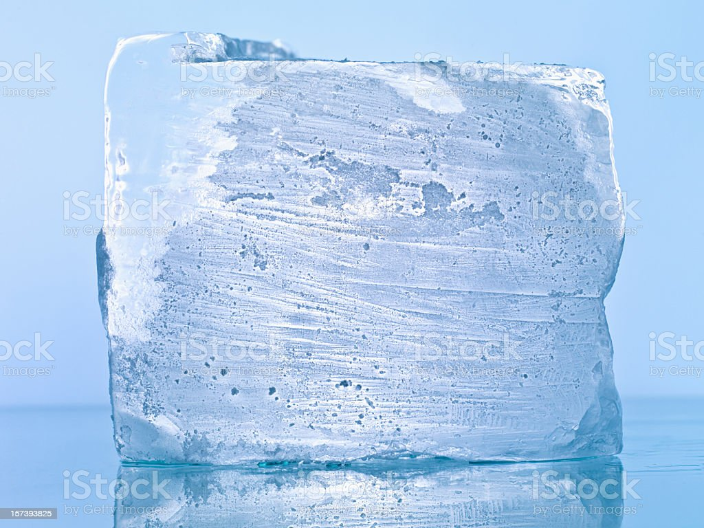 Close up of block of ice against blue background stock photo