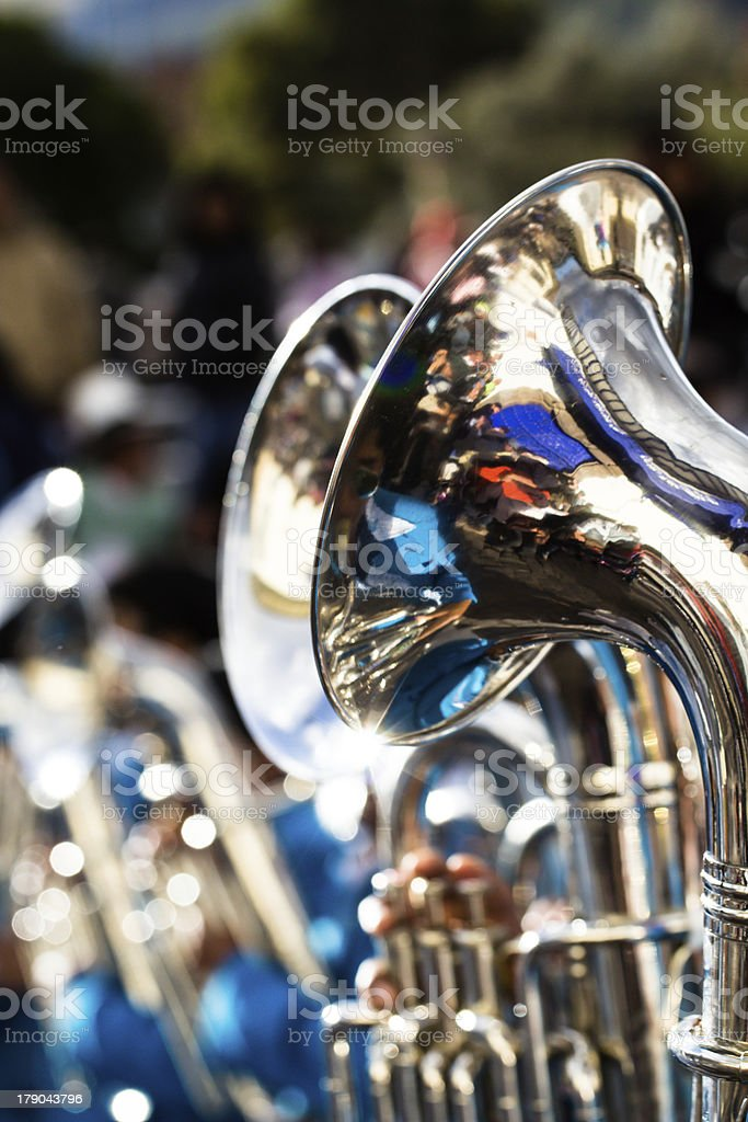 Close up of blue-suited marching band playing their trumpets stock photo