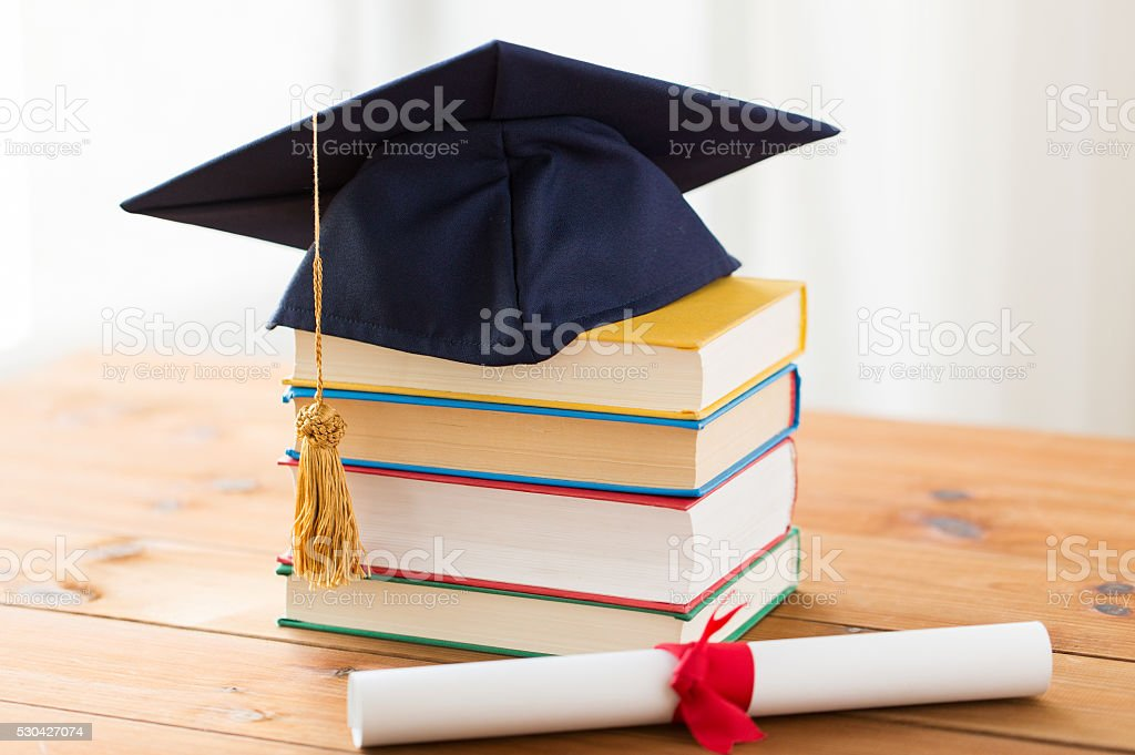 close up of books with diploma and mortarboard stock photo