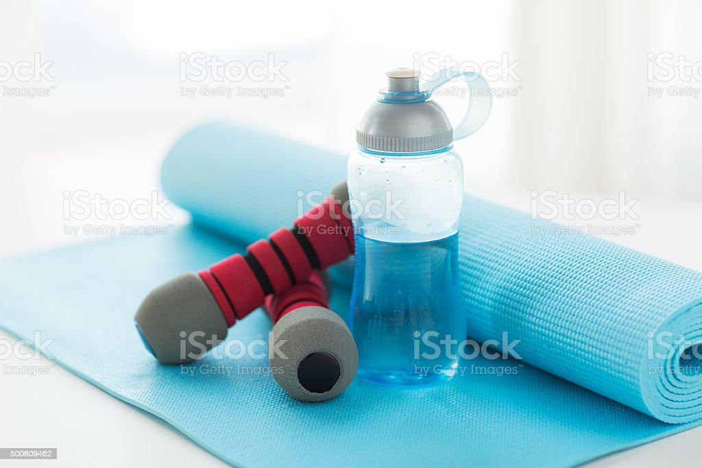 close up of bottle, dumbbells and sports mat stock photo