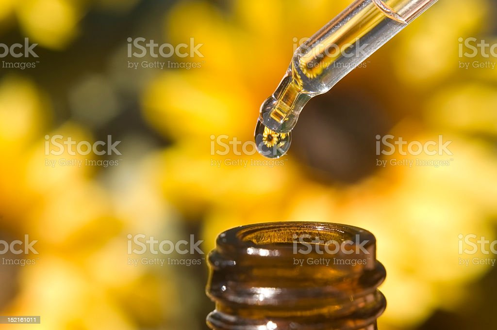 Close up of bottle top and pipette with sunflowers behind royalty-free stock photo