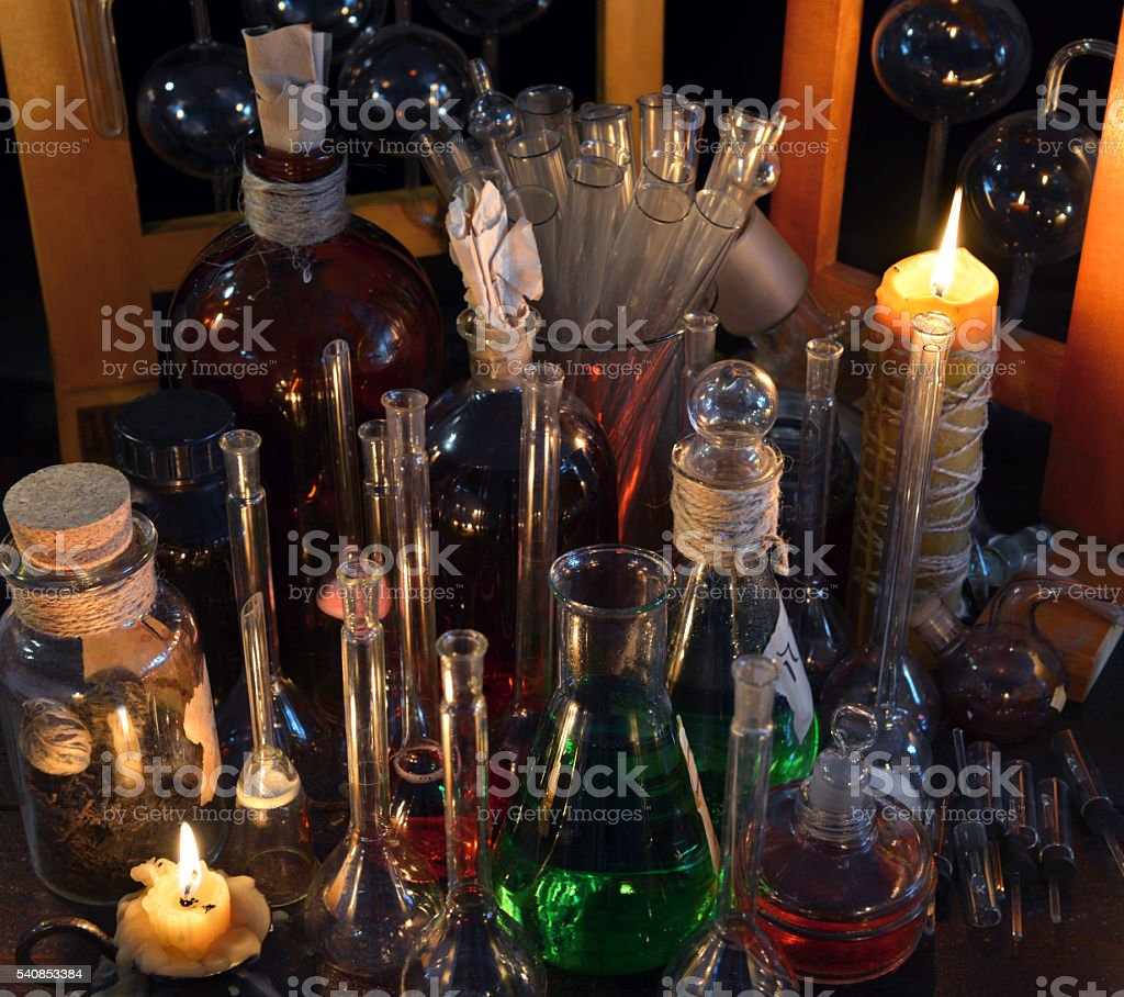 Close up of bottles, flask and candles in alchemy laboratory stock photo