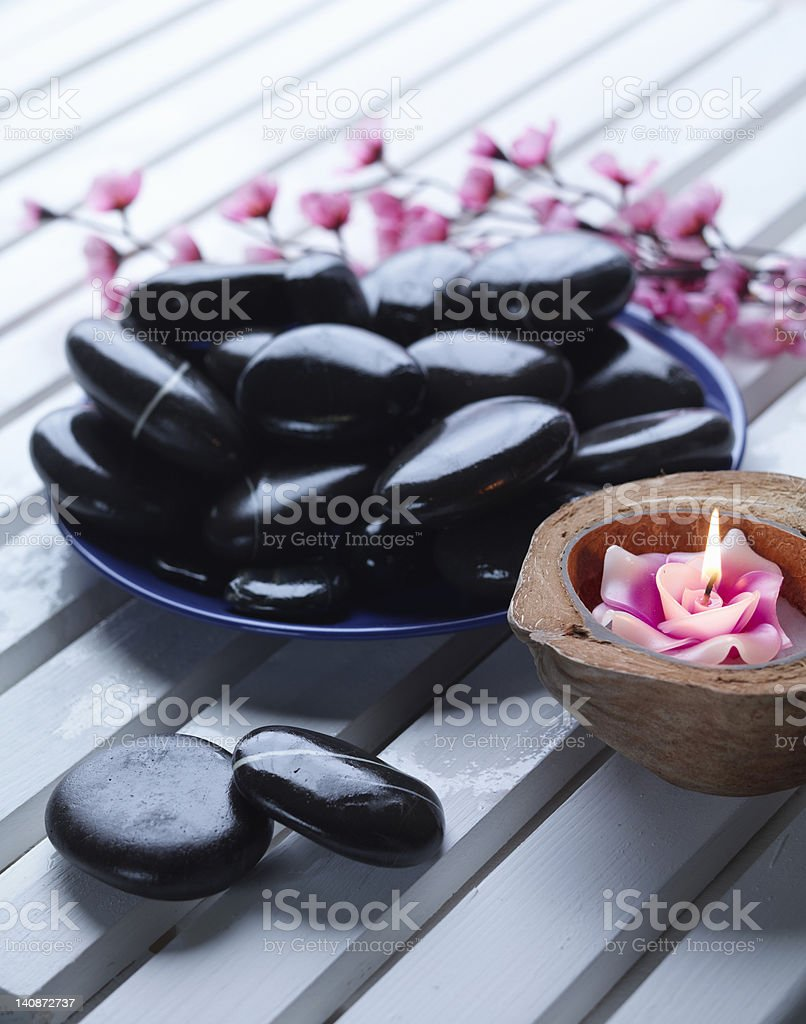 Close up of bowl of rocks and candle stock photo