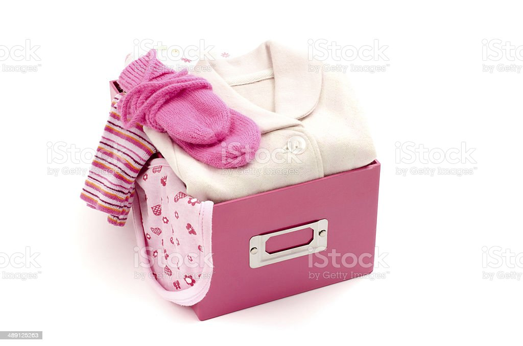 Close up of box with baby pink clean clothes isolated stock photo