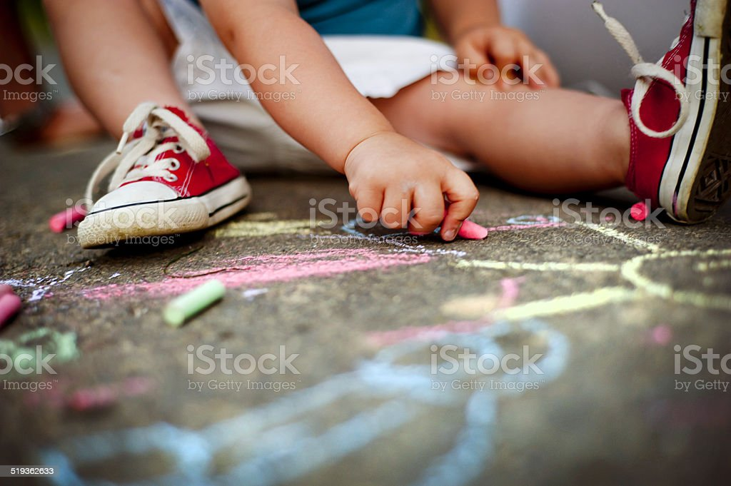 Close up of boy drawing with chalks stock photo