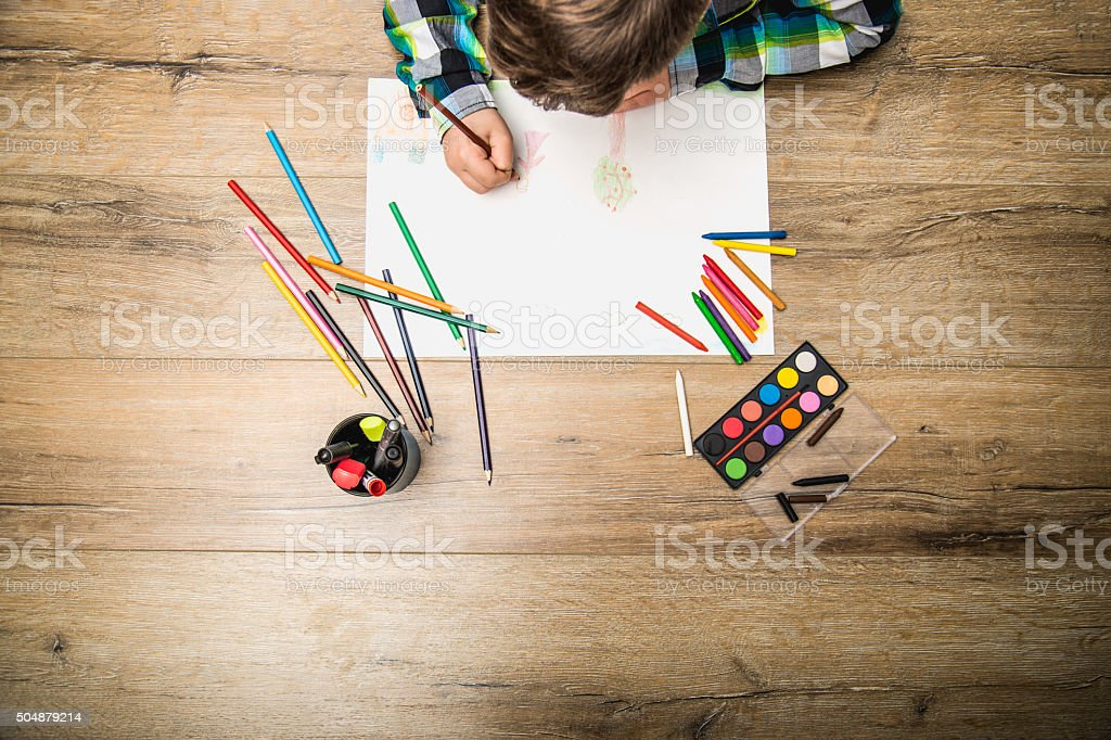 close up of  boy drawing with water color and crayons stock photo