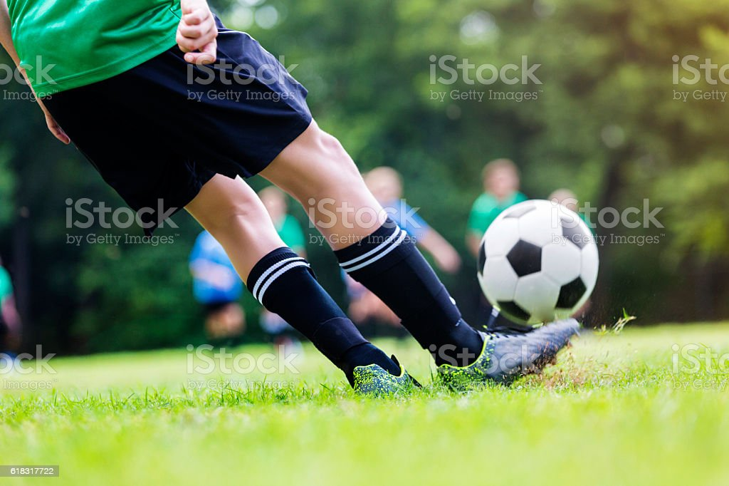 Close up of boy kicking soccer ball during game stock photo