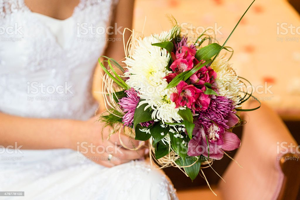 Close up of bride holding bouquet of flowers stock photo