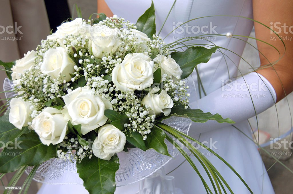 Close up of bride holding bouquet of white roses royalty-free stock photo