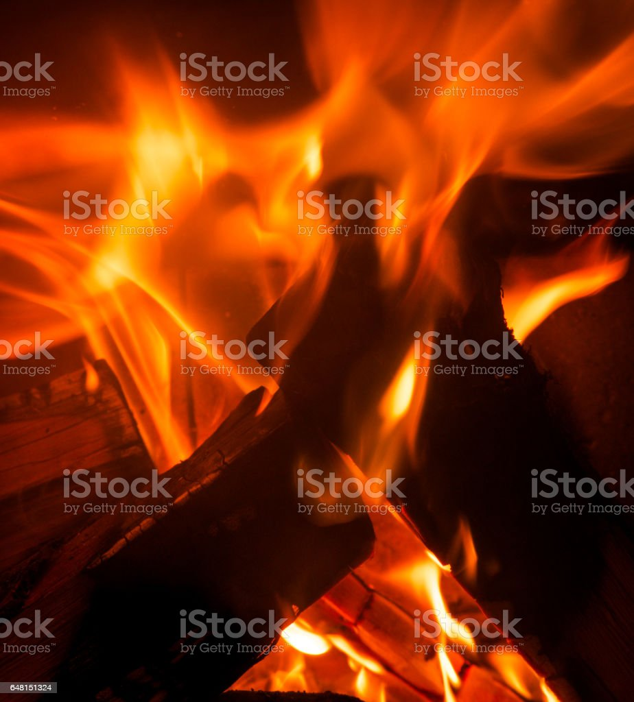 close up of bright orange flames burning in a wooden fire stock photo