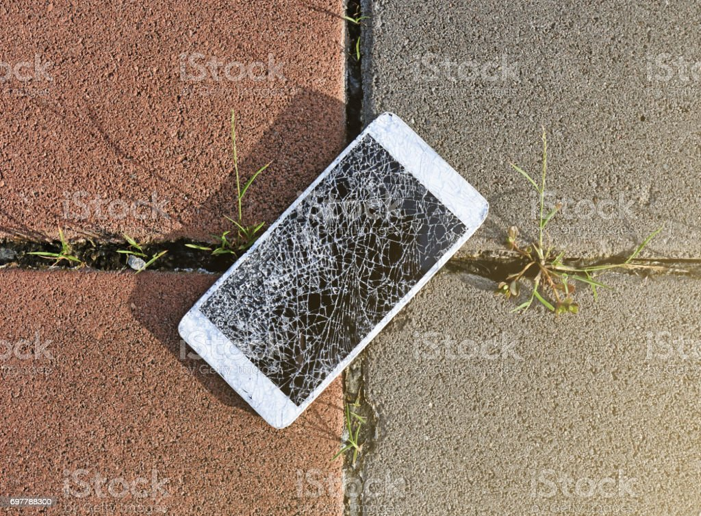 Close up of broken mobile phone drop on stone paved sidewalk outdoors stock photo