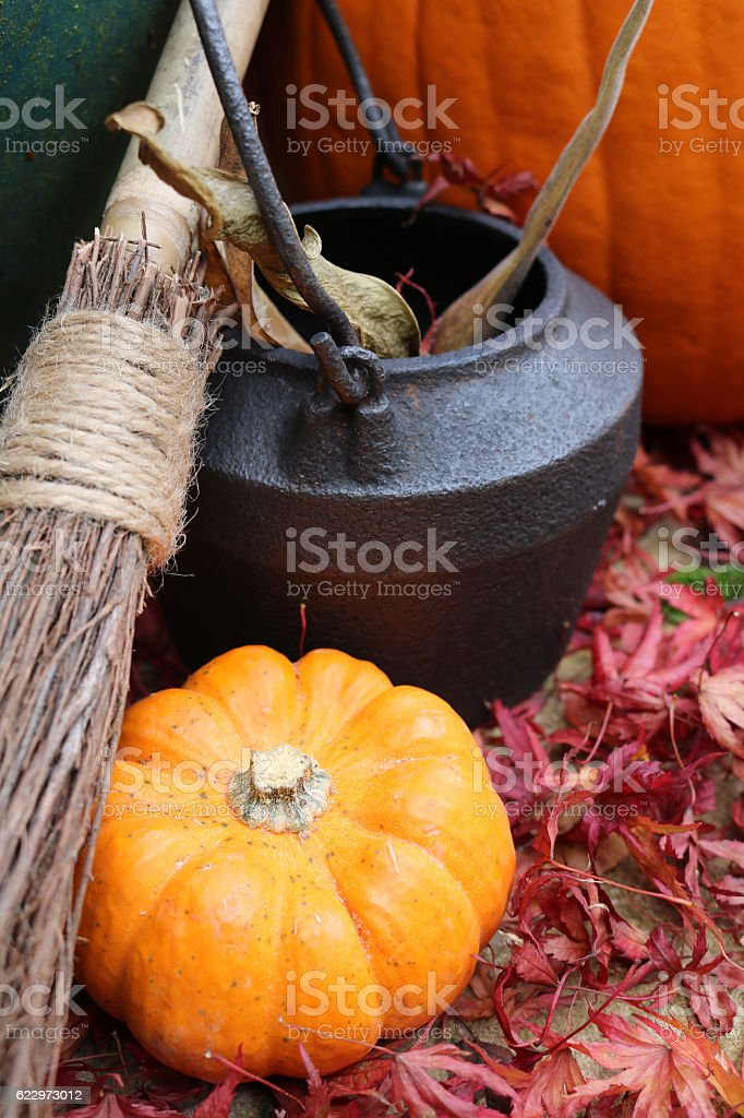 Close up of broomstick, cauldron and pumpkin stock photo