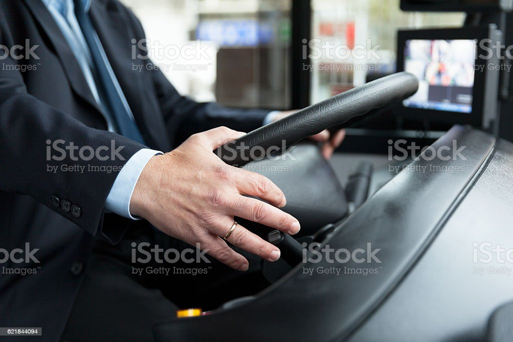 Close up of bus driver driving passenger bus stock photo