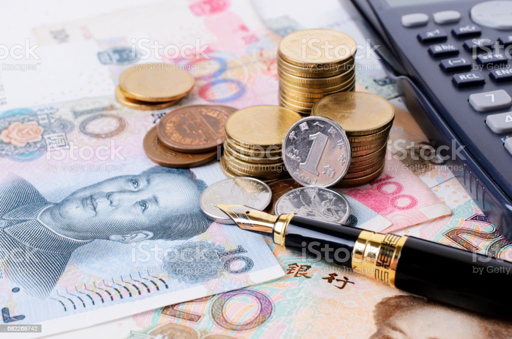 Close up of Business fountain pen and coins stack and china banknote stock photo