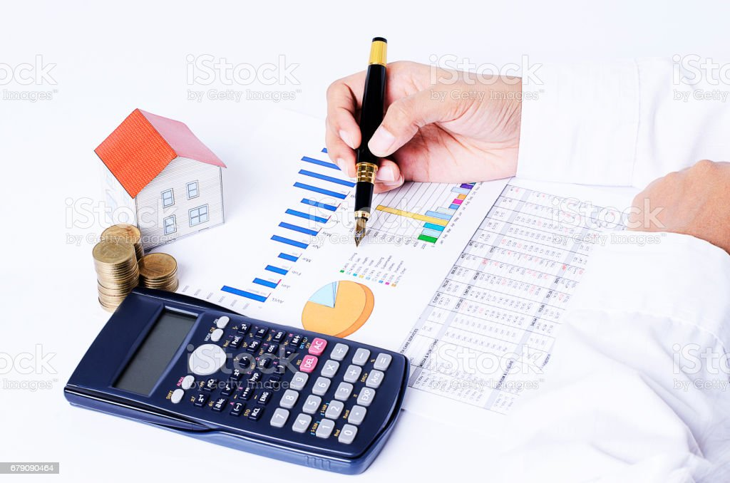 close up of business fountain pen on chart with house paper, coins stack and calculator for Mortgage loans concept stock photo