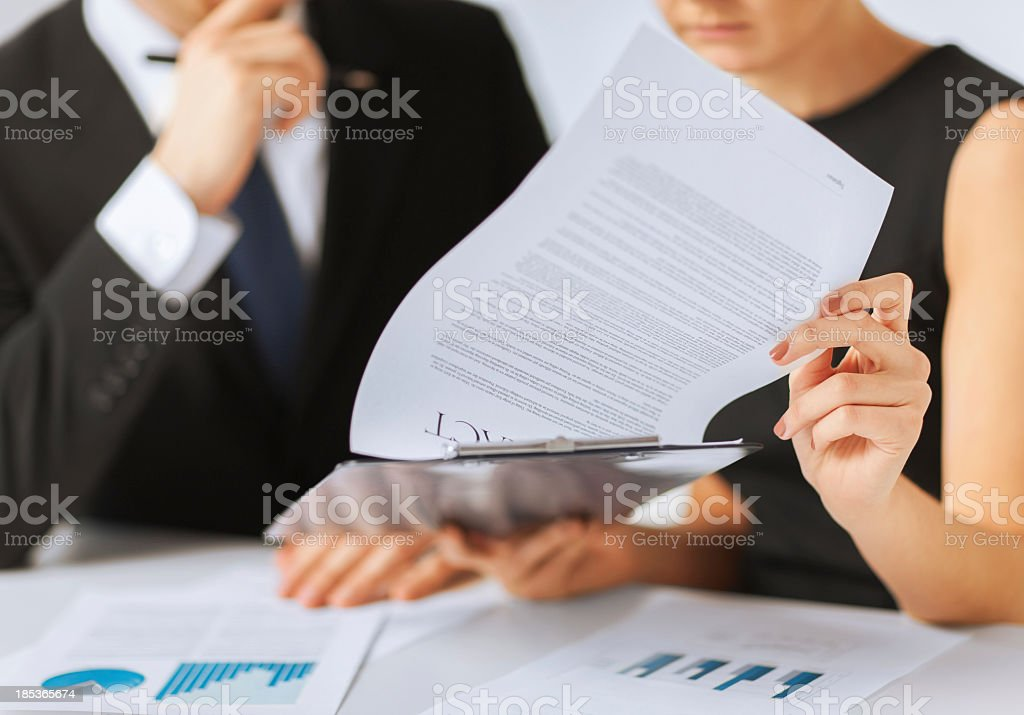 man and woman signing contract paper stock photo