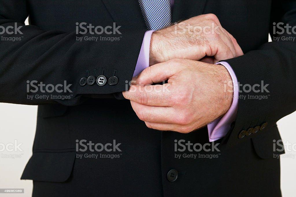 Gros plan d'un homme d'affaires ajuster ses boutons de manchette photo libre de droits