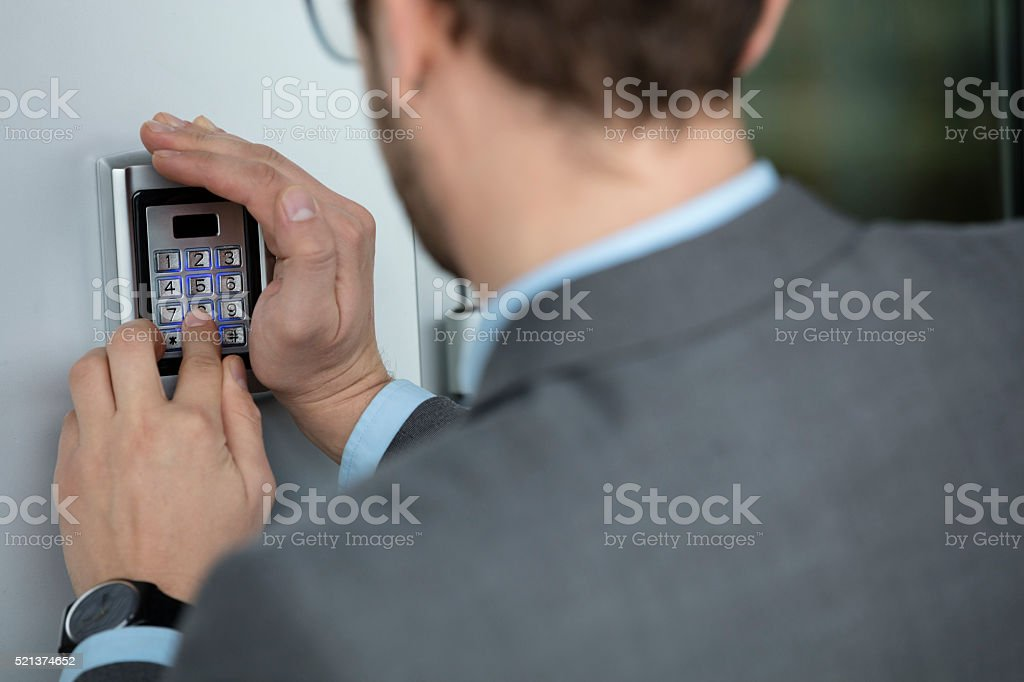 Close up of businessman hand pressing button on security system stock photo