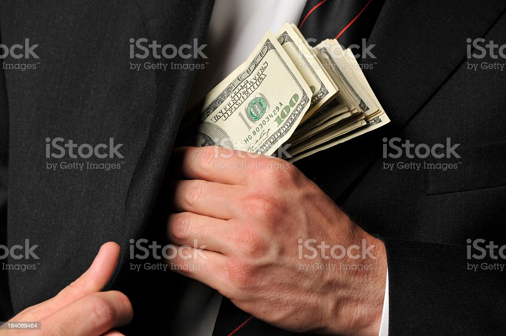 Close Up of Businessman Slipping Cash into His Suit Jacket stock photo