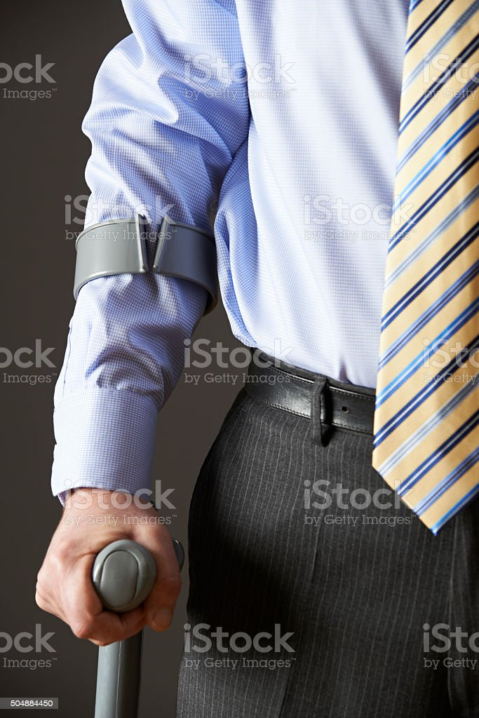 Close Up Of Businessman Using Crutch stock photo