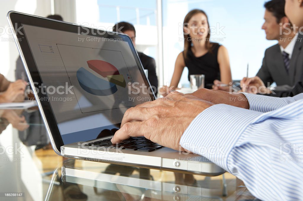 Close Up Of Businessman Using Laptop During Board Meeting royalty-free stock photo