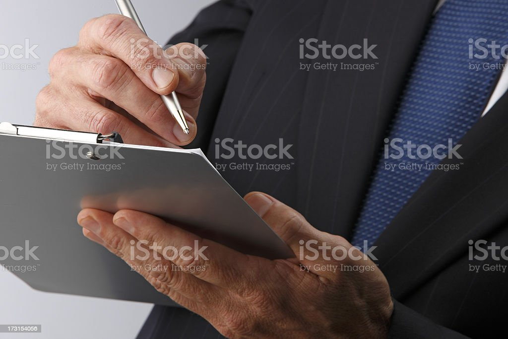 Close up of businessman writing clipboard royalty-free stock photo