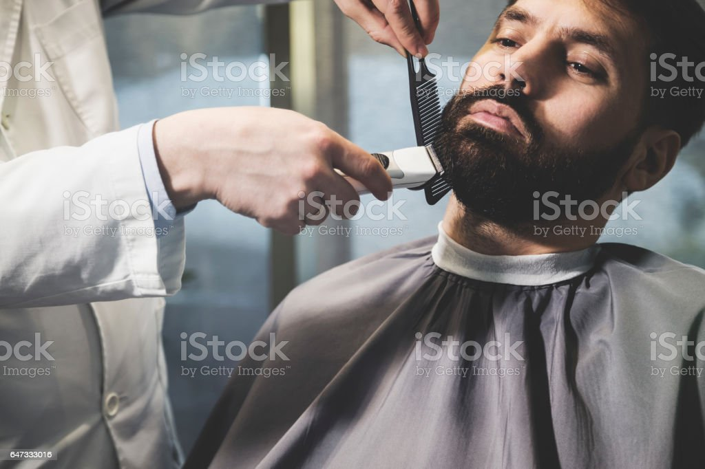 Close up of businessman's beard being trimmed stock photo