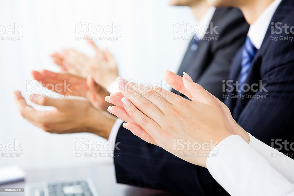 Close up of businesspeople clapping hands stock photo