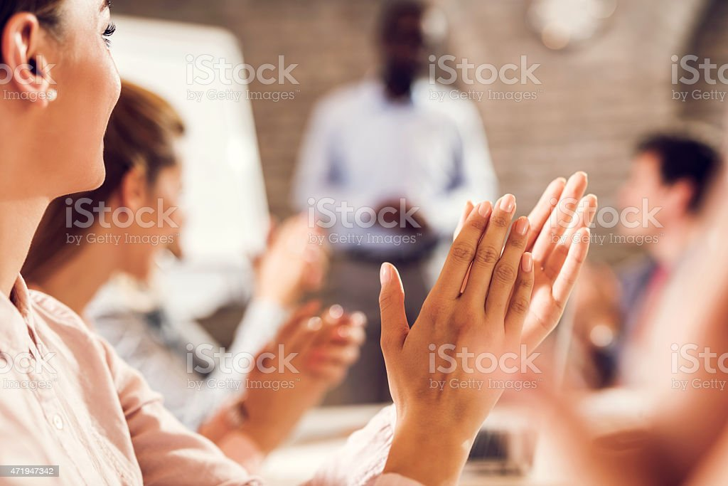 Close up of businesswoman applauding her colleague on good presentation. stock photo