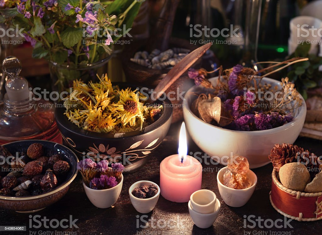 Close up of candle, herbs, flowers and berries stock photo