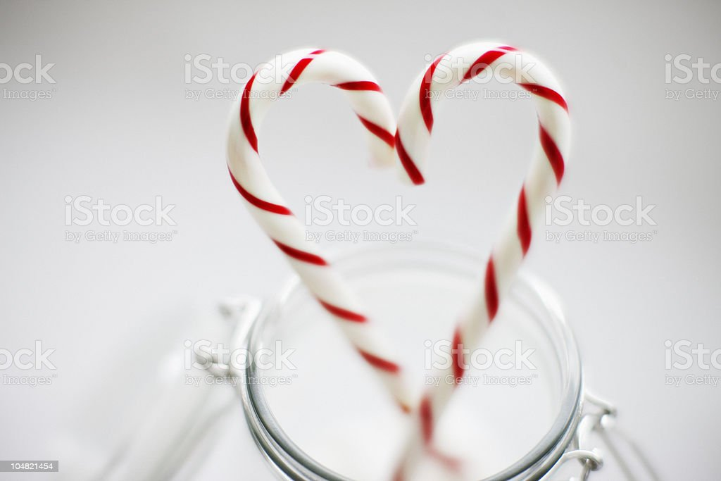 Close up of candy canes forming heart-shape stock photo