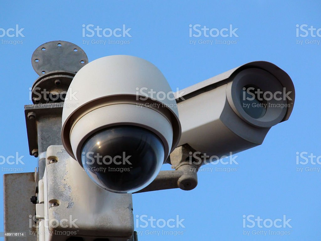 Close Up Of CCTV Road Security Camera Against Blue Sky stock photo