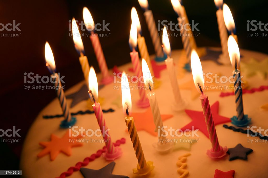 Close up of celebration cake with lit candles stock photo