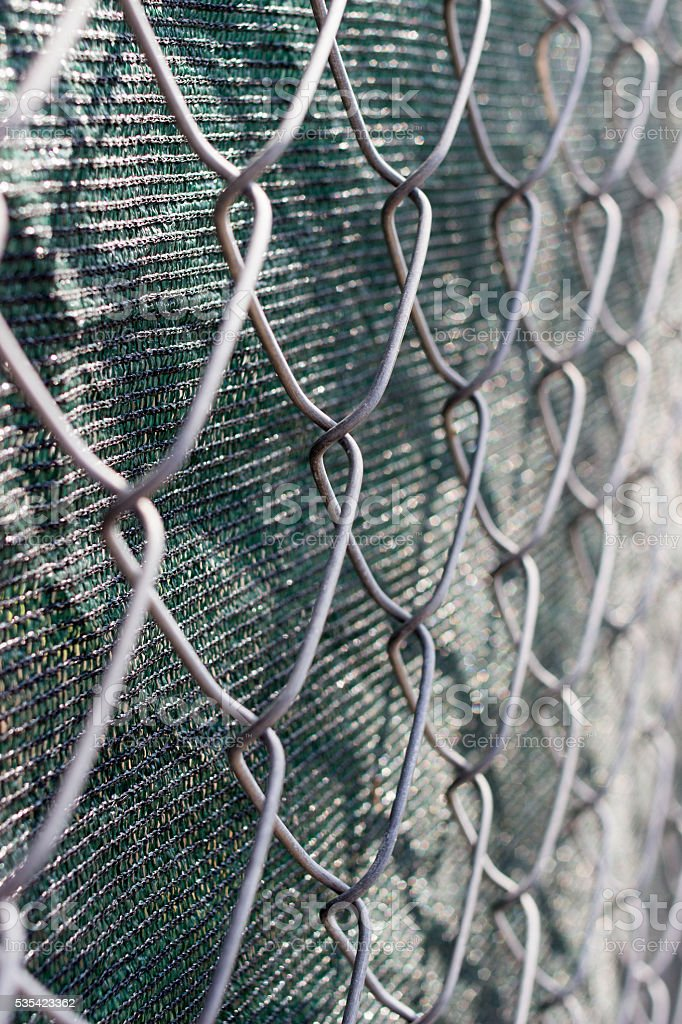 Close up of chain link fence with green fabric stock photo
