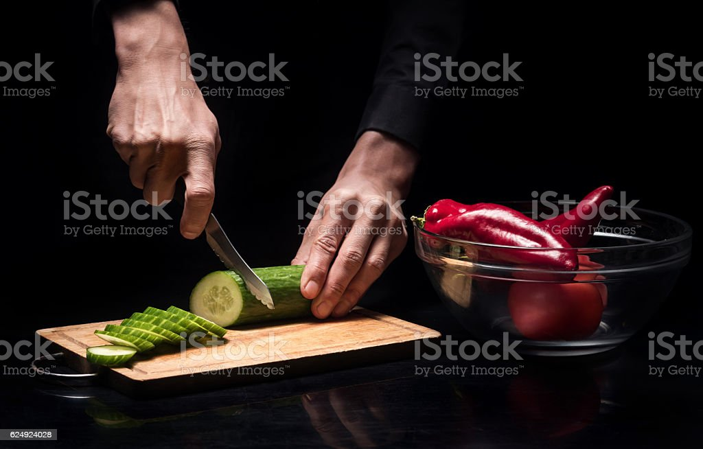 Close up of chef mans hands chopping vegetables stock photo