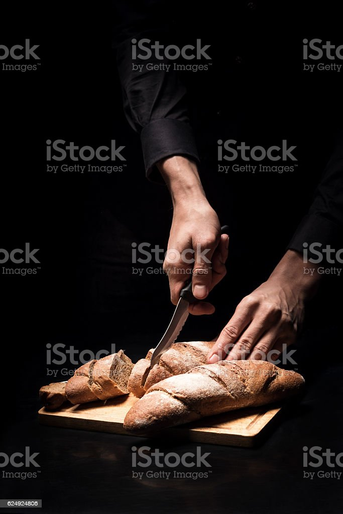 Close up of chefs hands chopping baguette on black background stock photo
