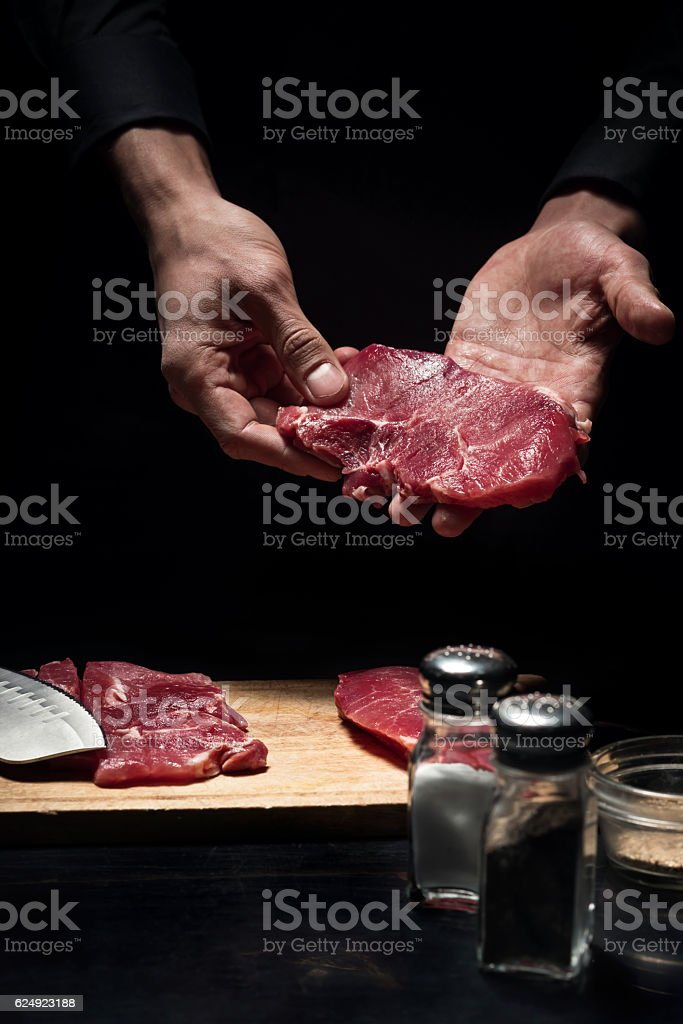 Close up of chefs hands holding meat stock photo