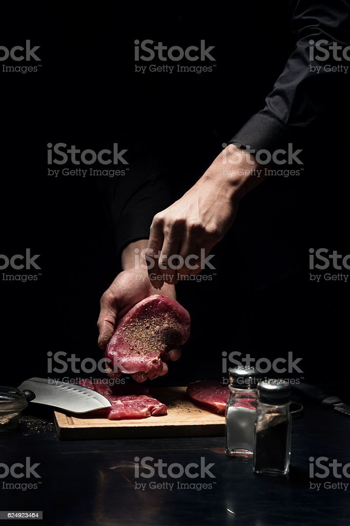 Close up of chefs hands spicing the meat stock photo