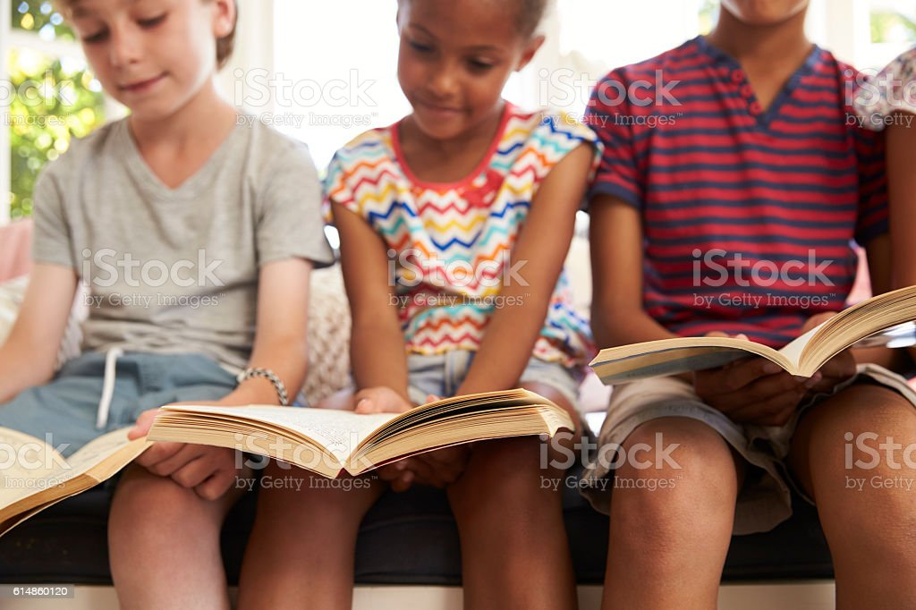 Close Up Of Children Reading On Window Seat stock photo