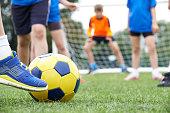 Close Up Of Children's Feet In Soccer Match